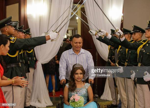 Juleydi Castillo enters the salon accompanied by her father during the 15th birthday party dance organized for cancer patients in Managua on October...
