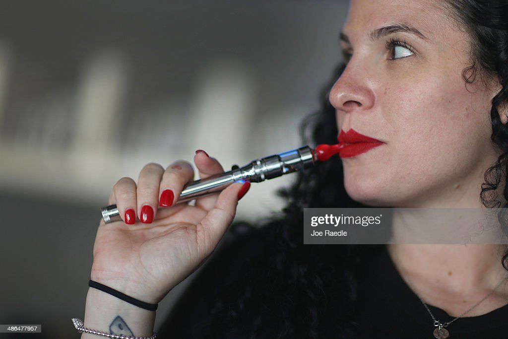 Julia Boyle enjoys an electronic cigarette as she waits for customers at the Vapor Shark store on April 24, 2014 in Miami, Florida. Brandon Leidel, CEO, Director of Operations Vapor Shark, said he welcomes the annoucement by the Food and Drug Administration that they are proposing the first federal regulations on electronic cigarettes, which would ban sales of the popular devices to anyone under 18 and require makers to gain FDA approval for their products.