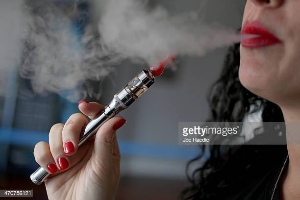 Julia Boyle enjoys an electronic cigarette at the Vapor Shark store on February 20 2014 in Miami Florida As the popularity of E cigarettes continue...