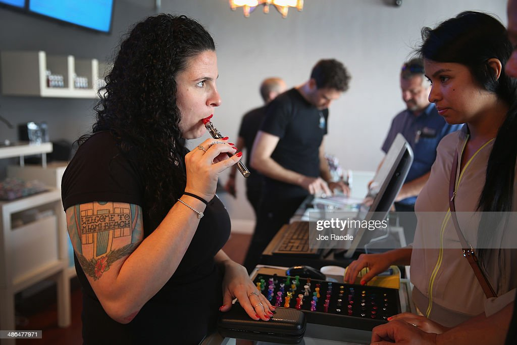 Julia Boyle (L) helps Marcela Guerra as she shops for an electronic cigarette at the Vapor Shark store on April 24, 2014 in Miami, Florida. Brandon Leidel, CEO, Director of Operations Vapor Shark, said he welcomes the annoucement by the Food and Drug Administration that they are proposing the first federal regulations on electronic cigarettes, which would ban sales of the popular devices to anyone under 18 and require makers to gain FDA approval for their products.