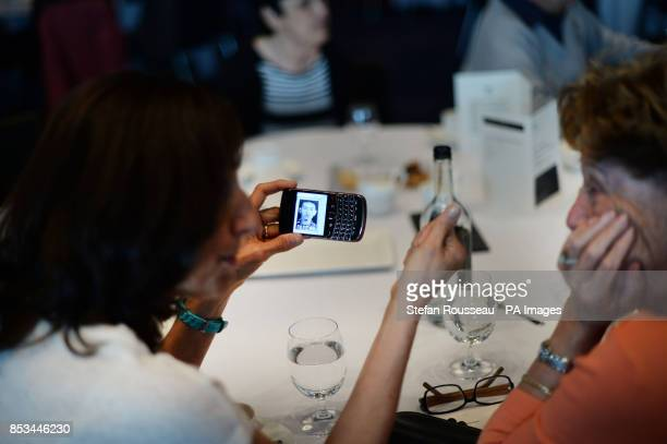 Julia Burton shows a picture on her mobile phone of her late father and Holocaust survivor David Herman whilst attending the Holocaust Commission...