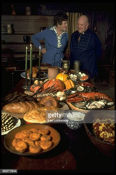 Julia Child and James Beard appear in good humor standing behind table arrayed w autumnal foods while appearing on TV show Revolutionary Recipes