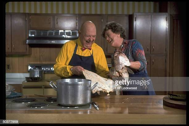 Julia Child and James Beard laughing together cleaning a large fish while appearing on TV show Revolutionary Recipes