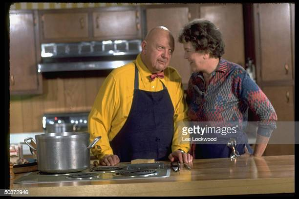 Julia Child and James Beard teasing each other w good humor in spotless kitchen setting while appearing on TV show Revolutionary Recipes