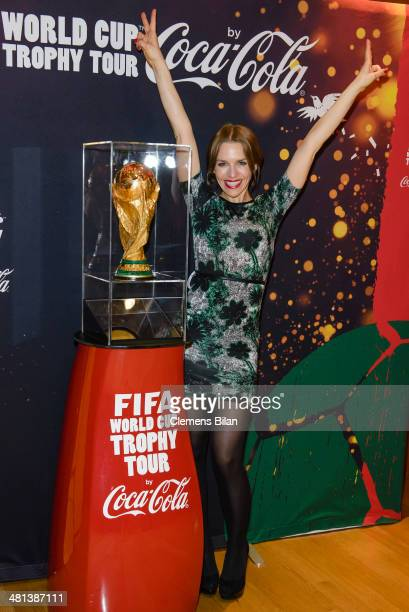 Julia Dietze poses with the trophy during a photocall at the Gala Night of the FIFA World Cup Trophy Tour on March 29 2014 in Berlin Germany