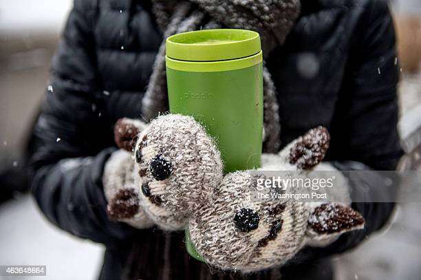 Julia Fox of Washington DC wears animal mittens to hold her coffee as light snow falls in Northwest on February 16 2015 in Washington DC The...