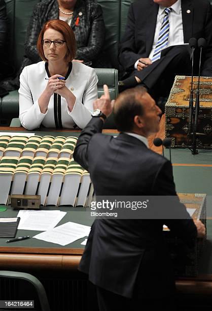 Julia Gillard Australia's prime minister left looks on as Tony Abbott Australia's opposition leader speaks during question time at Parliament House...