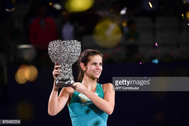 Julia Goerges of Germany celebrates with the trophy after her victory against Coco Vandeweghe of the US in the women's singles final at the Zhuhai...