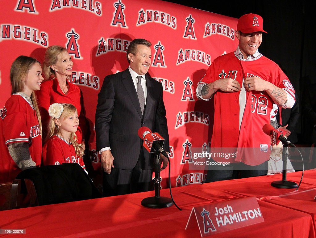 Julia Hamilton, Sierra Hamilton, Carole Moreno, Owner Arte Moreno of the Los Angeles Angels of Anaheim watch as Josh Hamilton #32 of the Los Angeles Angels of Anaheim puts on his new jersey during the press conference introducing Hamilton as the team's newest player at ESPN Zone at Downtown Disney on December 15, 2012 in Anaheim, California.