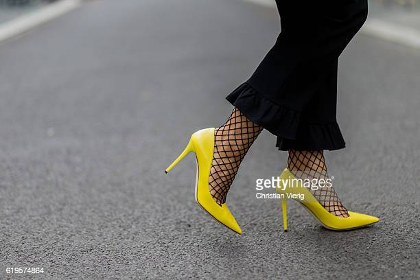 Julia Isabella Kuhne wears a black pants with ruffles from Zara yellow pumps from Jimmy Choo net tights on October 31 2016 in Berlin Germany
