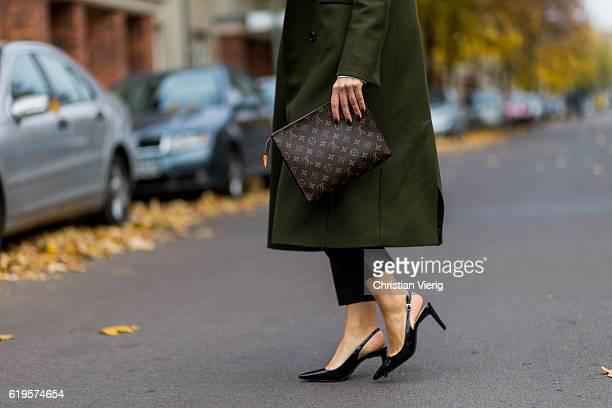 Julia Isabella Kuhne wears a khaki coat from Ivy Oak black pants from ZARA black slingback pumps from ZARA Louis Vuitton bag clutch on October 31...