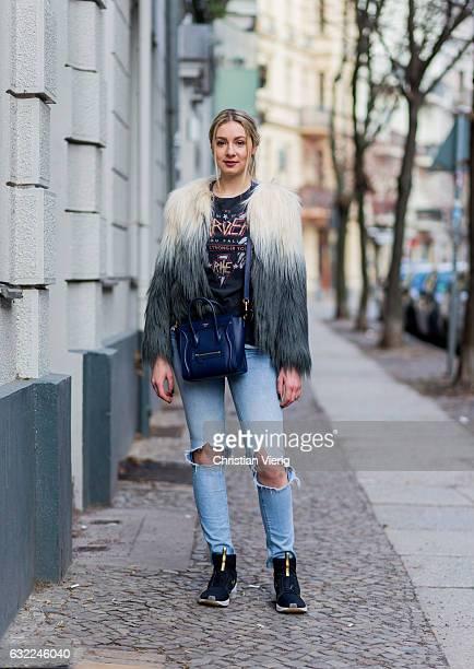 Julia Leopold wearing tshirt and ripped denim jeans Pull Bear fake fur jacket Topshop Puma sneaker blue Celine bag during the MercedesBenz Fashion...