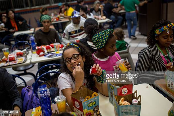 Julia Muniz from the Cantagalo 'favela' community enjoys a happy meal at McDonalds before heading to the Olympic Rugby 7's on August 11 2016 in Rio...