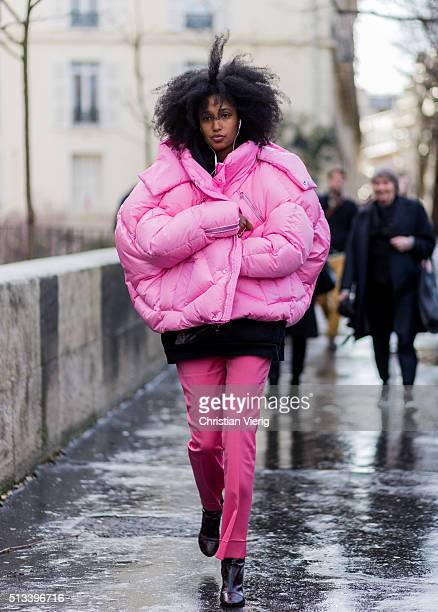 Julia Sarr Jamois wearing a huge pink feather down jacket and a black hoody pink pants and black Louis Vuitton boots outside Rochas during the Paris...