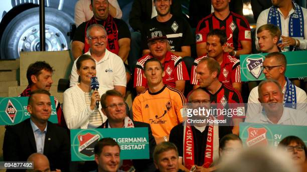 Julia Scharf reporter speaks to members of Sportfreunde Dorfmerkingen after being chosen for the match against RB Leipzig during the DFB Cup Draw at...