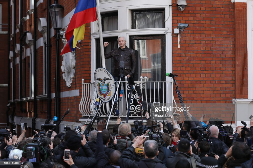 Julian Assange, founder of WikiLeaks, holds up a fist before speaking to media and supporters from a balcony at the Ecuadorian embassy in London, U.K., on on Friday, May 19, 2017. Assange hailed a Swedish decision to drop a rape probe against him, but said he won't leave the Ecuadorian embassy in London where he has sought refuge for the past five years as long as he remains a target in the U.S. and U.K. Photographer: Luke MacGregor/Bloomberg via Getty Images