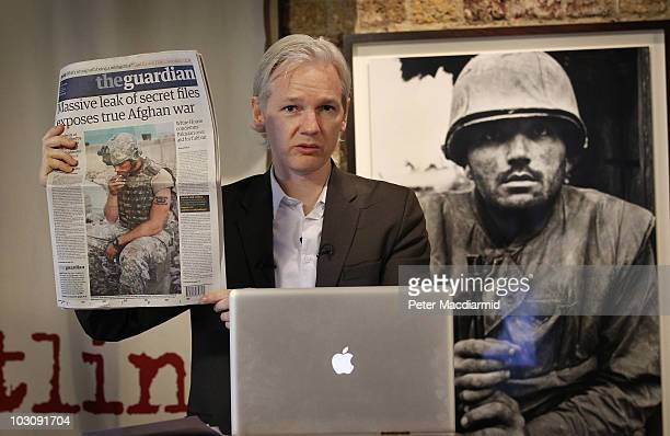 Julian Assange of the WikiLeaks website holds up a copy of The Guardian newspaper as he speaks to reporters in front of a Don McCullin Vietnam war...