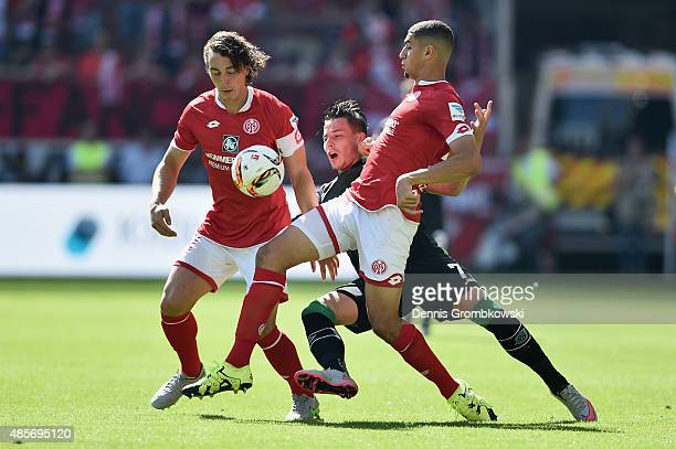 Julian Baumgartlinger and Leon Balogun of 1 FSV Mainz 05 challenge Edgar Prib of Hannover 96 during the Bundesliga match between 1 FSV Mainz 05 and...