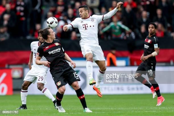Julian Baumgartlinger of Leverkusen and Thiago Alcantara do Nascimento of Bayern battle for the ball during the Bundesliga match between Bayer 04...