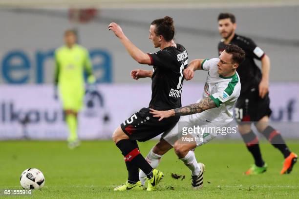 Julian Baumgartlinger of Leverkusen is challenged by Robert Bauer of Bremen during the Bundesliga match between Bayer 04 Leverkusen and Werder Bremen...