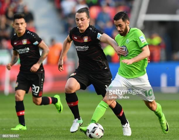 Julian Baumgartlinger of Leverkusen is challenged by Yunus Malli of Wolfsburg during the Bundesliga match between Bayer 04 Leverkusen and VfL...