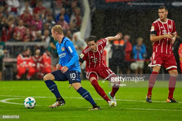 Julian Brandt and Sebastian Rudy of Muenchen battle for the ball during the Bundesliga match between FC Bayern Muenchen and Bayer 04 Leverkusen at...