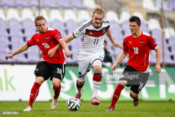Julian Brandt of Germany challenges Markus Blutsch and Martin Rasner of Austria during the UEFA Under19 European Championship semifinal between...