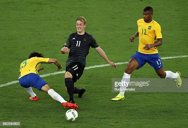 Julian Brandt of Germany is challenged by Rodrigo Caio of Brazil during the Men's Football Final between Brazil and Germany at the Maracana Stadium...