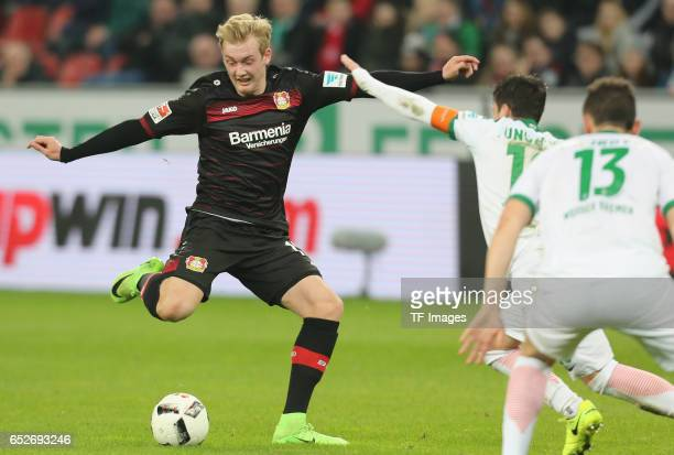 Julian Brandt of Leverkusen and Zlatko Junuzovic and Milos Veljkovic of Bremen battle for the ball during the Bundesliga soccer match between Bayer...