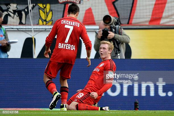 Julian Brandt of Leverkusen celebrates with team mate Chicharito after scoring the opening goal during the Bundesliga match between 1 FC Koeln and...