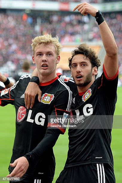 Julian Brandt of Leverkusen celebrates with team mate Hakan Calhanoglu after scoring the opening goal during the Bundesliga match between 1 FC Koeln...