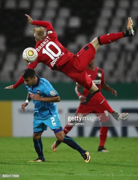Julian Brandt of Leverkusen falls over Burak Camoglu of Karlsruhe during the DFB Cup first round match between Karlsruher SC and Bayer Leverkusen at...