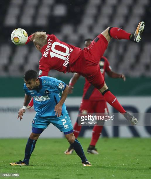 Julian Brandt of Leverkusen falls over Burak Camoglu of Karlsruhe during the DFB Cup first round match between Karlsruher SC and Bayer Leverkusen at...
