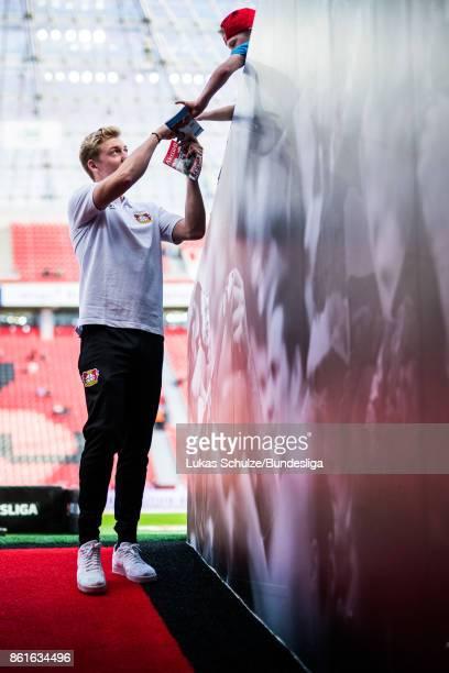Julian Brandt of Leverkusen gives a autograph to a fan prior to the Bundesliga match between Bayer 04 Leverkusen and VfL Wolfsburg at BayArena on...