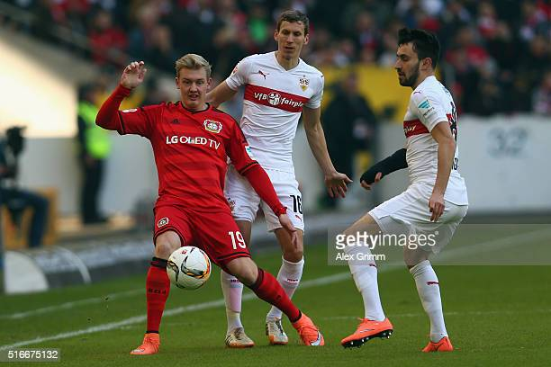 Julian Brandt of Leverkusen is challenged by Florian Klein and Lukas Rupp of Stuttgart during the Bundesliga match between VfB Stuttgart and Bayer...