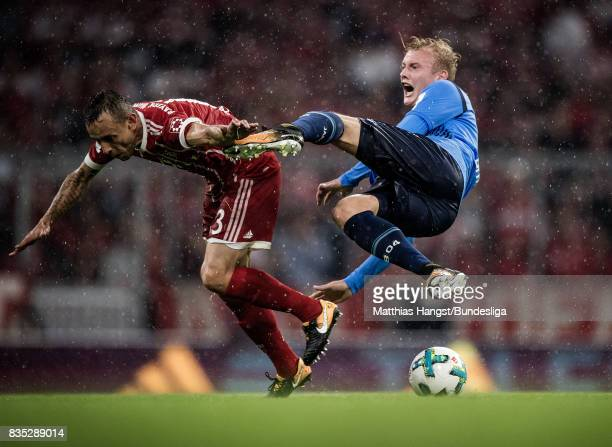 Julian Brandt of Leverkusen is challenged by Rafinha of FC Bayern Muenchen during the Bundesliga match between FC Bayern Muenchen and Bayer 04...