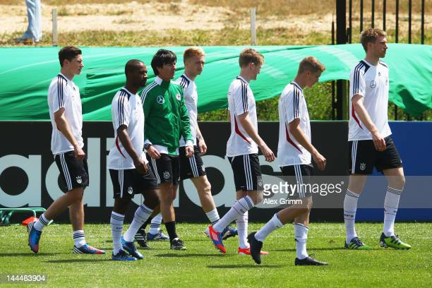 Julian Draxler Cacau head coach Joachim Loew Andre Schuerrle Lars Bender and Per Mertesacker walk over the pitch during a Germany training session at...