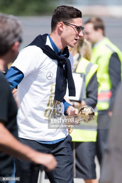 Julian Draxler carries the trophy as he departs the plane carrying the Germany National Football Team during the arrival at Frankfurt International...