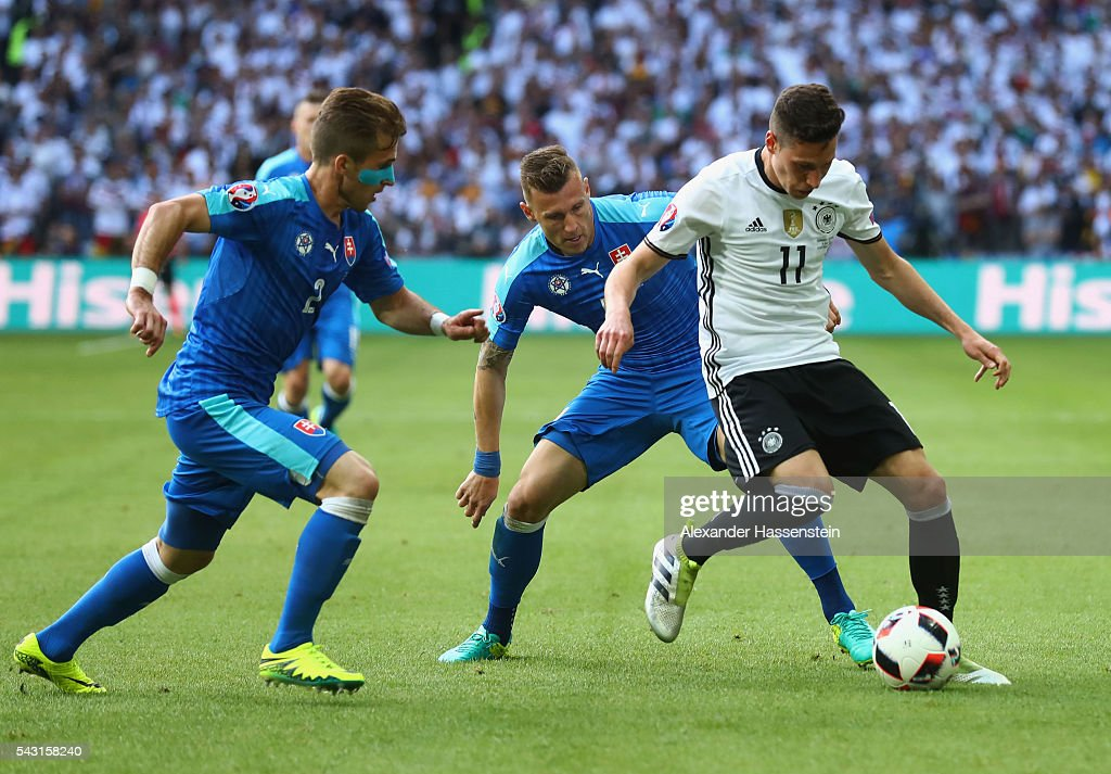 Julian Draxler (R) of Germany competes for the ball against Peter Pekarik (L) and Jan Durica (C) of Slovakia during the UEFA EURO 2016 round of 16 match between Germany and Slovakia at Stade Pierre-Mauroy on June 26, 2016 in Lille, France.