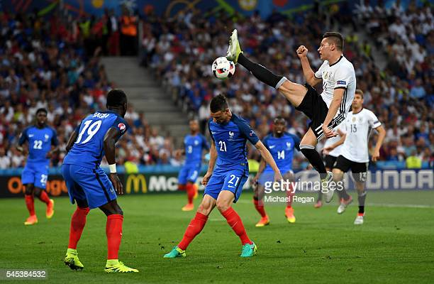 Julian Draxler of Germany leaps to control the ball next to Laurent Koscielny of France during the UEFA EURO semi final match between Germany and...