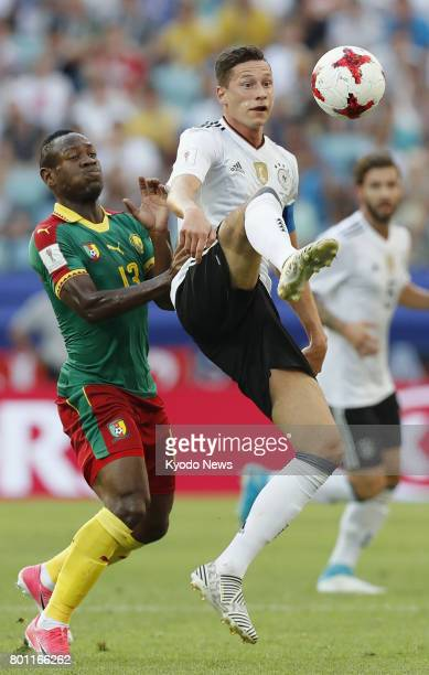 Julian Draxler of Germany tries to hold off Christian Bassogog of Cameroon during the first half of a Group B match at the Confederations Cup in...