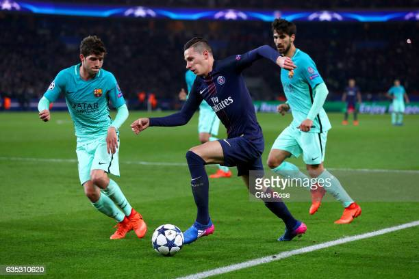 Julian Draxler of Paris SaintGermain runs with the ball under pressure from Sergi Roberto and Andre Gomes of Barcelona during the UEFA Champions...