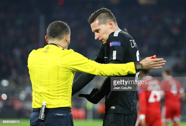 Julian Draxler of PSG argues with referee Cuneyt Cakõr of Turkey during the UEFA Champions League group B match between Bayern Muenchen and Paris...