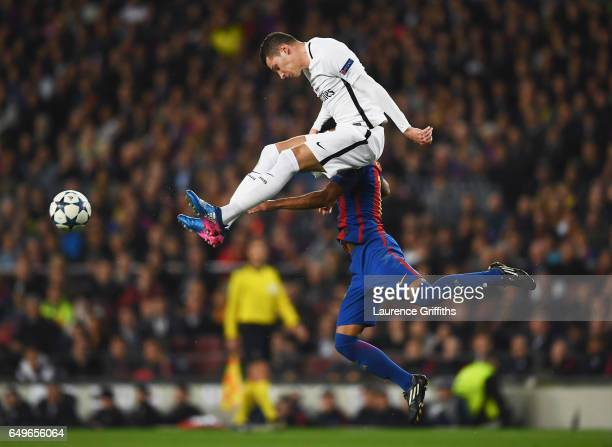 Julian Draxler of PSG jumps with Rafinha of Barcelona during the UEFA Champions League Round of 16 second leg match between FC Barcelona and Paris...