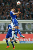 Julian Draxler of Schalke and Thorben Marx of Moenchengladbach go up for a header during the Bundesliga match between Borussia Moenchengladbach and...