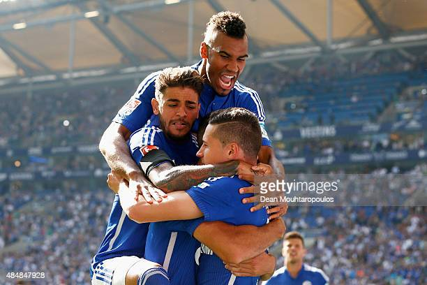 Julian Draxler of Schalke celebrates scoring his teams first goal of the game with Junior Caicara and Eric Maxim ChoupoMoting during the Bundesliga...