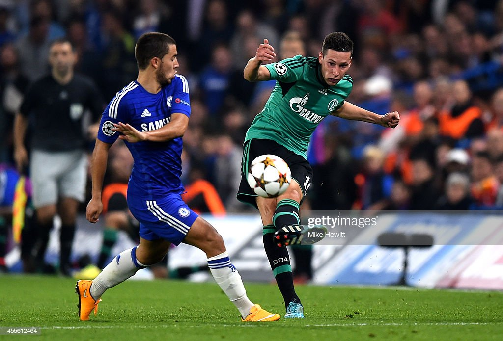 Julian Draxler of Schalke crosses the ball as Eden Hazard of Chelsea closes in during the UEFA Champions League Group G match between Chelsea and FC Schalke 04 on September 17, 2014 in London, United Kingdom.