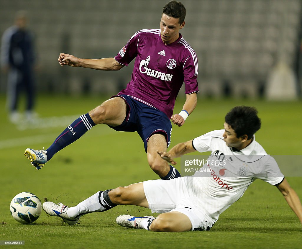 Julian Draxler (L) of Schalke is challenged by Jung Soo Lee of Qatar's al-Sadd, during their friendly football match in Doha on January 6, 2013. Schalke is in Qatar for a week-long training camp before the beginning of the new season of the German Bundesliga after the winter break. AFP PHOTO/KARIM SAHIB
