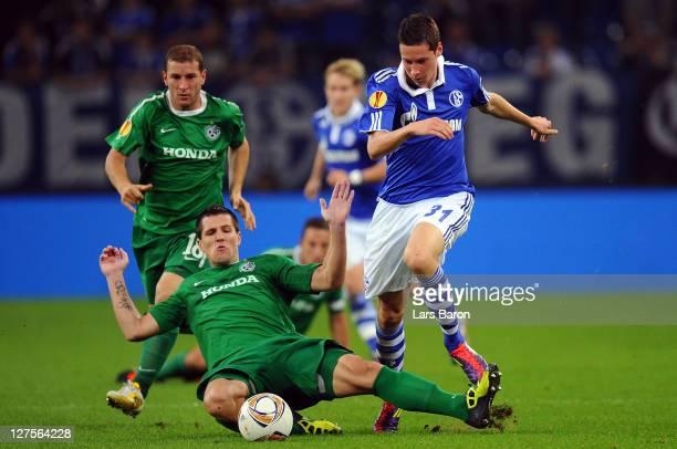 Julian Draxler of Schalke is challenged by Jurica Buljat of Haifa during the UEFA Europa League group J match between FC Schalke 04 and Maccabi Haifa...