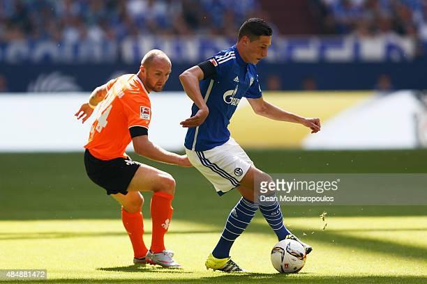 Julian Draxler of Schalke runs with the ball against Konstantin Rausch of Darmstadt during the Bundesliga match between FC Schalke 04 and SV...